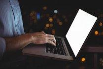 Sección media del hombre usando el ordenador portátil en casa - foto de stock