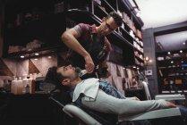 Barber applying cream on client beard in barber shop — Stock Photo