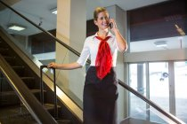 Female staff with luggage talking on mobile phone on escalator in airport — Stock Photo