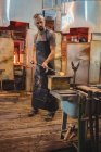 Glassblower shaping a molten glass at glassblowing factory — Stock Photo