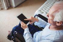 Homme âgé assis sur fauteuil roulant et utilisant une tablette numérique à la maison — Photo de stock