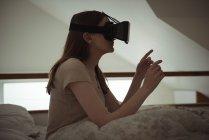 Mujer usando auriculares de realidad virtual en la cama en casa - foto de stock
