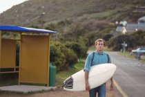 Portrait of a man carrying a surfboard walking along road — Stock Photo