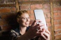 Жінка, стоячи проти цегляну стіну і беручи на selfie їй мобільному телефоні — стокове фото