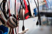 Varios cables de datos y auriculares colgando en un centro de reparación - foto de stock