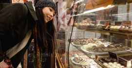 Woman looking at desserts at dessert counter in bakery counter — Stock Photo