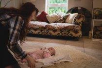 Mère jouant avec bébé sur le sol dans le salon à la maison — Photo de stock