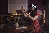 Mujer haciendo gestos mientras usa auriculares de realidad virtual en casa - foto de stock