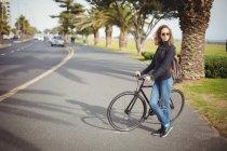 Mujer de pie con la bicicleta en la carretera - foto de stock