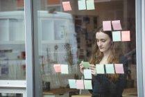 Escrita executiva feminina em notas pegajosas no escritório — Fotografia de Stock