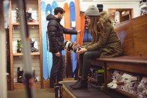 Женщина примеряет лыжный ботинок, а мужчина выбирает лыжи в магазине — стоковое фото