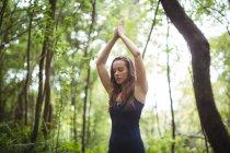 Женщина медитирует в позе лотоса в лесу — стоковое фото
