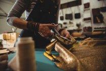 Meados de seção de artesã cortando couro na oficina — Fotografia de Stock