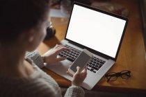 Frau benutzt Handy und Laptop zu Hause auf dem Tisch — Stockfoto