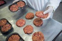 Primer plano de las empanadas de embalaje de carniceros en la fábrica de carne - foto de stock