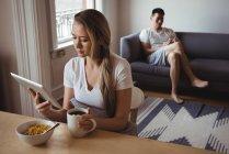 Femme utilisant une tablette numérique tout en prenant le petit déjeuner à la maison — Photo de stock