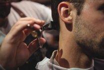 Close-up de homem recebendo cabelo aparado por cabeleireiro com tesoura na barbearia — Fotografia de Stock