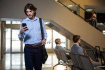 Пасажирів, що використання мобільного телефону у зону очікування в аеропорту — стокове фото