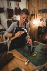 Craftswoman hammering leather in workshop interior — Stock Photo