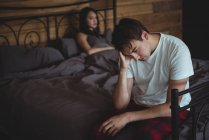 Upset couple ignoring each other after fight on bed in bedroom — Stock Photo