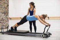Allenatrice donna che assiste la donna con esercizio di stretching sul riformatore in palestra — Foto stock