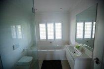 Empty bathroom with hand wash basin and bathtub at home — Stock Photo