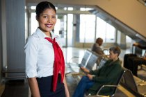 Smiling female staff standing at airport terminal — Stock Photo