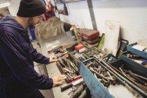 Mechanic looking at tools in repair garage — Stock Photo