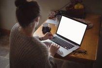 Mujer usando el ordenador portátil en la mesa en la cocina en casa - foto de stock