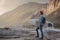 Seitenansicht eines Mannes tragen ein Surfbrett stehend auf dem Seeweg in der Abenddämmerung — Stockfoto