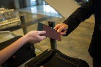 Flughafenmitarbeiterinnen geben den Passagieren im Flughafenterminal die Bordkarte — Stockfoto