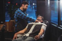 Парикмахер накрывает клиента полотенцем в парикмахерской — стоковое фото