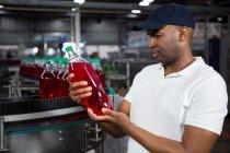 Молоді чоловіки працівник оглядають сік пляшку заводі — стокове фото