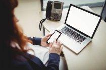 Embarazada mujer de negocios utilizando el teléfono móvil en la oficina - foto de stock