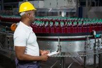 Вид збоку чоловічого працівника огляду пляшок сік заводі — стокове фото