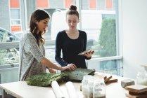 Бизнес-руководители, изучающие искусственное покрытие при использовании цифрового планшета в офисе — стоковое фото