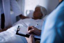 Medico maschile che scrive una prescrizione sugli appunti in ospedale — Foto stock