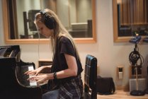 Donna che suona un pianoforte in studio di musica — Foto stock
