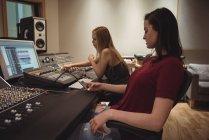 Engenheiros de áudio usando telefone celular conectado ao mixer de som no estúdio de gravação — Fotografia de Stock
