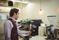 Mann benutzt Portafilter bei der Zubereitung von Kaffee in Kaffeemaschine — Stockfoto