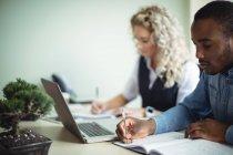 Executivos de negócios tomando notas ao usar laptop no escritório — Fotografia de Stock