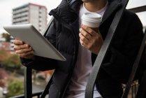 Metà sezione dell'uomo utilizzando tablet digitale mentre prende il caffè in balcone — Foto stock