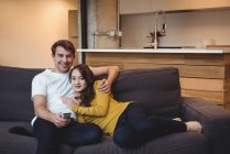 Smiling couple sitting on a sofa watching TV in living room at home — Stock Photo