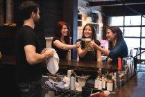Щасливі друзями тостів з келихи пива на барна стійка — стокове фото