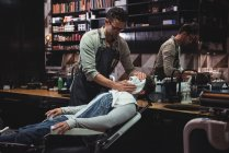Barber applying hot towel on client face in barber shop — Stock Photo