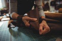 Mittelteil einer Kunsthandwerkerin, die in der Werkstatt an einem Stück Leder arbeitet — Stockfoto