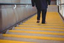 Empresario con un diario bajando escaleras en la oficina - foto de stock
