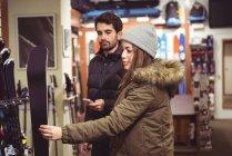 Casal selecionando esqui juntos em uma loja — Fotografia de Stock