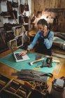 Artisanat utilisant un ordinateur portable tout en parlant sur téléphone portable dans l'atelier — Photo de stock