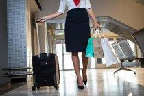 Airhostess marche avec sac trolley et sacs à provisions au terminal de l'aéroport — Photo de stock